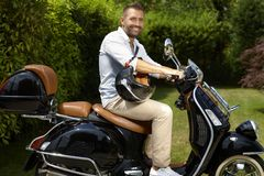 Happy casual man riding black scooter stock image
