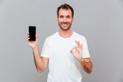 Happy casual man showing blank smartphone screen and okay gesture Stock Photography