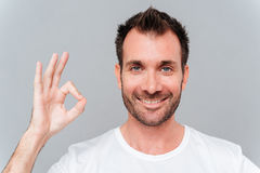 Happy casual man showing ok sign with fingers Royalty Free Stock Photography