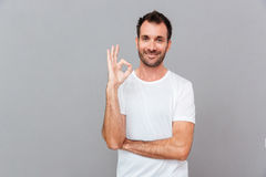 Happy casual man showing ok sign with fingers Stock Image