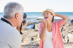 Happy casual man taking a photo of partner by the sea Stock Image