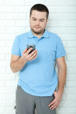 Happy casual man using smartphone standing near brick wall. Young handsome man thought Royalty Free Stock Photography