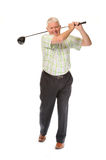 Happy casual mature golfer swinging a club Royalty Free Stock Images
