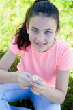 Happy casual preteen smelling a daisy. At outside Royalty Free Stock Photography