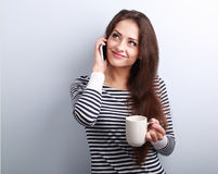 Happy casual thinking woman talking on mobile phone and holding Royalty Free Stock Photos