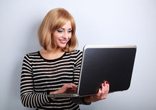 Happy casual woman holding and looking in laptop in hand and typ Royalty Free Stock Photos