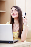 Happy casual woman shopping online. Beautiful young woman shopping on-line with credit card and laptop Royalty Free Stock Photos