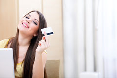Happy casual woman shopping online. Beautiful young woman shopping on-line with credit card and laptop Royalty Free Stock Image