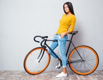 Happy casual woman standing with bicycle Royalty Free Stock Image