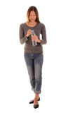 Happy casual woman standing and opening a  bottle of  water on w Stock Image