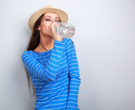 Happy casual woman in summer hat drinking pure water from bottle Stock Images