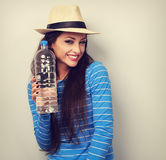 Happy casual woman in summer hat holding bottle of pure water an Stock Photos