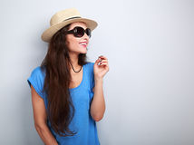 Happy casual woman in sun glasses and hat looking up on blue bac. Kground with empty copy space Royalty Free Stock Photos