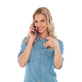 Happy casual woman talking on the phone and pointing finger Royalty Free Stock Photography