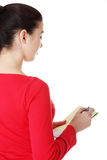 Happy casual woman writing on a piece of paper. Back view. Stock Photos
