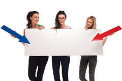 Happy casual women pointing arrows to a big blank board Royalty Free Stock Image
