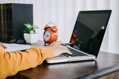 Happy casual young asian woman working in home or small office with using a laptop and document report on desk as a freelancer stock image