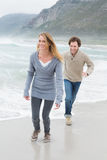 Happy casual young couple running at beach Stock Photo