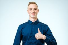 Happy casual young man showing thumbs up gesture. Isolated on white background Royalty Free Stock Photo