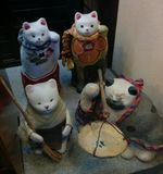 Happy cat sculptures in traditional dress and activities. Stock Photos