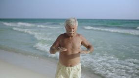 Happy Caucasian American male senior enjoying his outdoor lifestyle on beach and doing eexercising USA 4k stock video