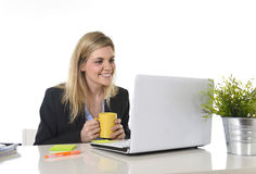 Happy Caucasian blond business woman working on laptop computer at modern office desk Stock Image