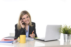 Happy Caucasian blond business woman working talking on mobile phone at office computer desk Royalty Free Stock Photo