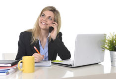 Happy Caucasian blond business woman working talking on mobile phone at office computer desk Royalty Free Stock Photos
