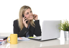 Happy Caucasian blond business woman working talking on mobile phone at office computer desk Stock Image