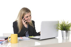 Happy Caucasian blond business woman working talking on mobile phone at office computer desk Stock Images
