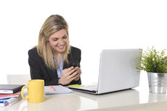 Happy Caucasian blond business woman working using mobile phone at office computer desk Royalty Free Stock Photos