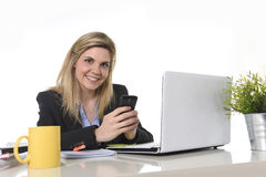 Happy Caucasian blond business woman working using mobile phone at office computer desk Royalty Free Stock Images