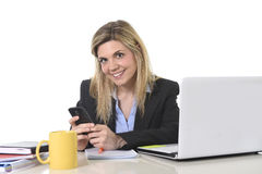 Happy Caucasian blond business woman working using mobile phone at office computer desk Stock Images