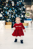 Happy Caucasian blonde baby girl toddler in red dress standing walking by New Year tree Stock Images