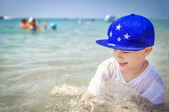 Happy caucasian boy is bathing in sea water on beach against are swimming people on horison. Summer vacation on sunny day. Tropical holidays with childs Royalty Free Stock Images