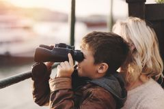 Happy caucasian boy watching into distantance by binoculars with Stock Photo
