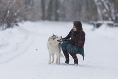 Happy Caucasian Brunette Girl With Husky Dog Outside in Winter Forest Stock Photo