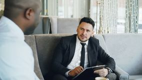 Happy Caucasian businessman laughing, gesticulating and discussing his startup project with business partner while stock footage