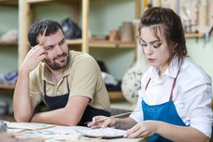 Happy Caucasian Ceramists Glazing and Painting Ceramic Clay tile. S in Workshop Together. Horizontal image Stock Photography