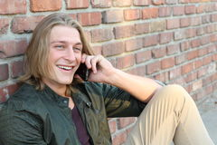 Happy Caucasian college boy talking on mobile phone.  Stock Photo