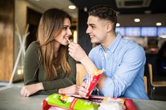 Happy caucasian couple eating french fries in fast food and have fun royalty free stock photography