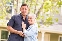 Happy Caucasian Couple in Front of House. Happy Caucasian Couple in Front of a New House royalty free stock photo