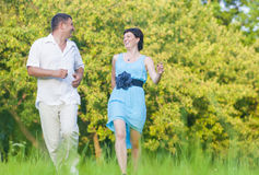 Happy caucasian Couple Having Good Time Outdoors Running Together. Couple Relationships Concepts and Ideas.Happy caucasian Couple Having Good Time Outdoors Royalty Free Stock Photography