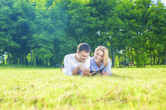 Happy Caucasian Couple in Love Lying on the Grass Outdoors. Read Stock Photo
