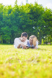 Happy Caucasian Couple in Love Lying on the Grass Outdoors. Read Royalty Free Stock Photo