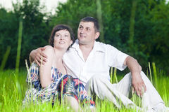 Happy Caucasian Couple Relaxing Together. Family Relationships. Happy Caucasian Couple Relaxing Together Outdoors on Grass in Park. Sitting Embraced.Horizontal Royalty Free Stock Images
