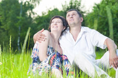 Happy Caucasian Couple Relaxing Together. Family Relationships. Happy Caucasian Couple Relaxing Together Outdoors on Grass in Park. Sitting Embraced.Horizontal Royalty Free Stock Image