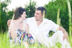 Happy Caucasian Couple Relaxing Together Outdoors Embracing. Family Relationships. Happy Caucasian Couple Relaxing Together Outdoors on Grass in Park. Sitting Stock Images
