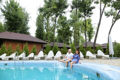 Happy caucasian couple sitting near white chaise longue, swiming pool and wooden house. stock image