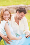 Happy caucasian Couple Sitting Together Outdoors While Using PDA Royalty Free Stock Photo